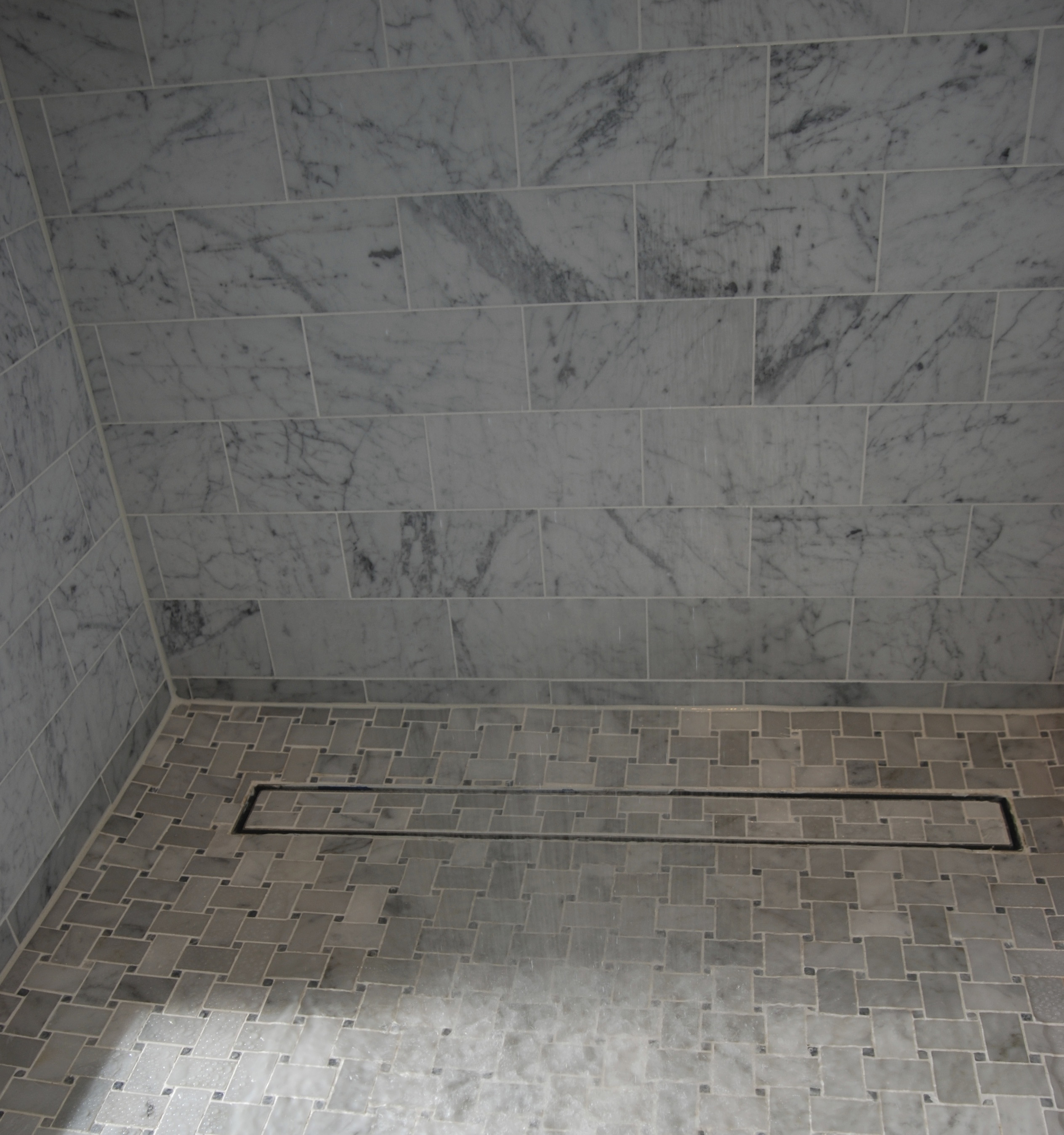 LUXE_Linear_Drain_Nice_Closeup_or_Gray_Tile_Shower_300_Media. Photo  Courtesy: LUXE Linear Drains
